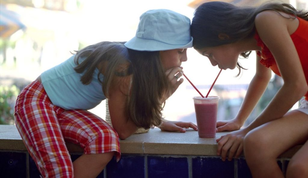teen girls sharing a smoothie