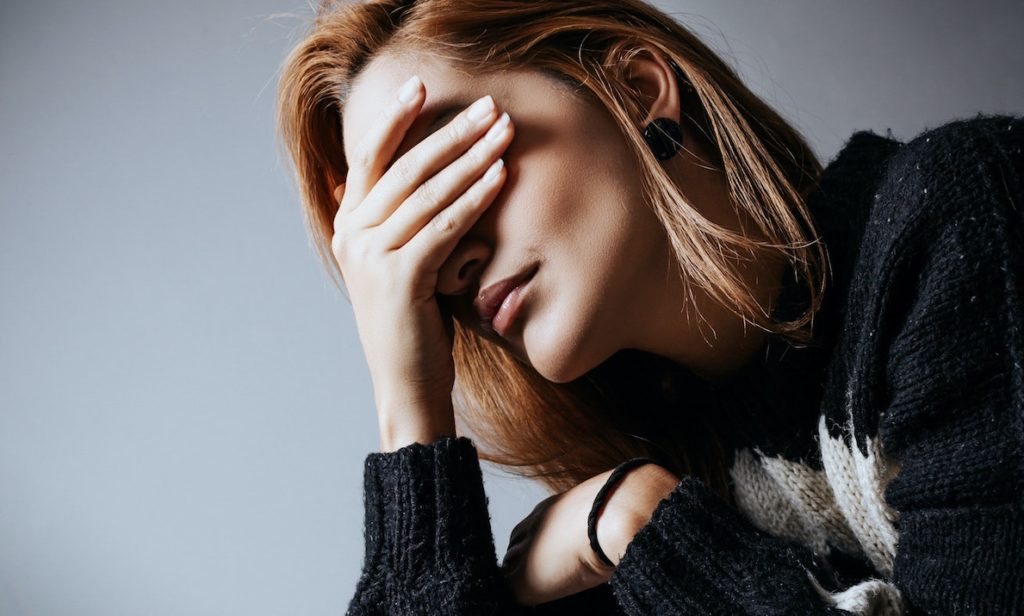 young woman covering her face in shame