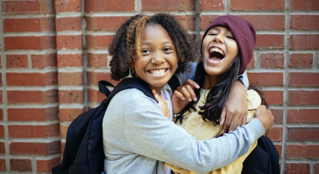 Two encouraging girls lifting each other up