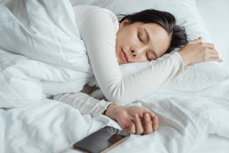 Teenage Girl Sleeping in Bed with White Covers